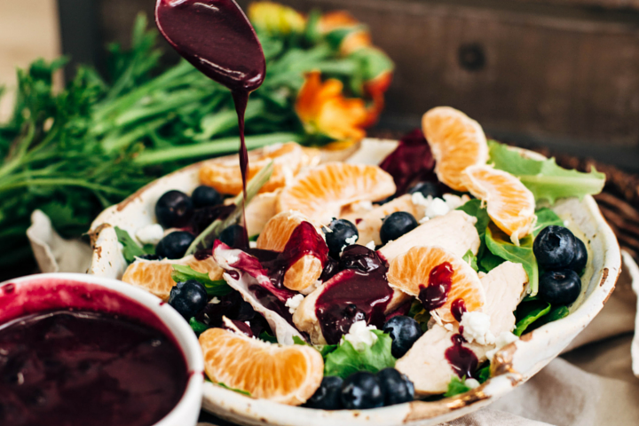Homemade Blueberry Vinaigrette Dressing Over a Green Salad with Chicken, Orange Slices and Blueberries